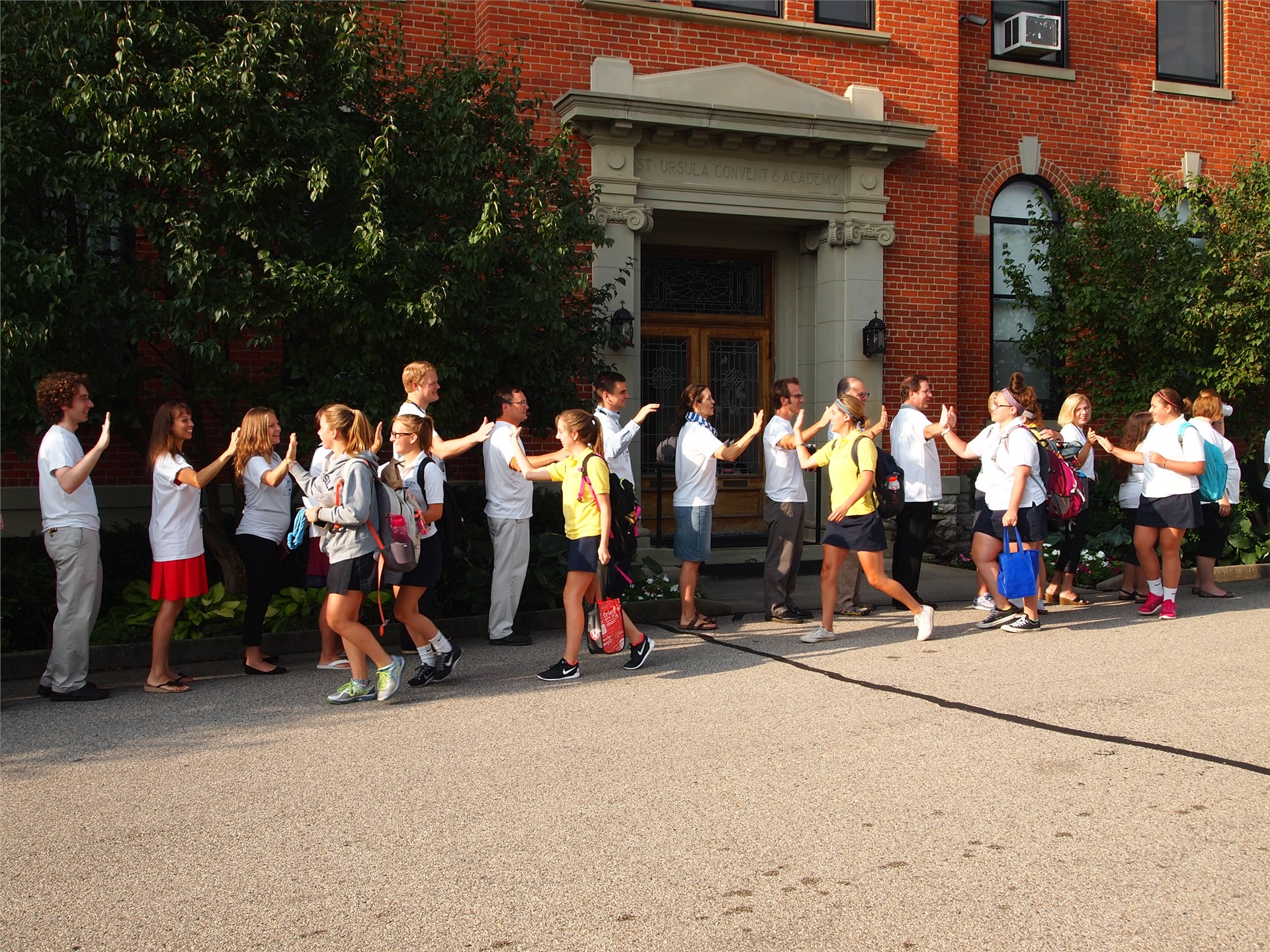 Faculty and Staff Welcome the Students with High Fives to a New School Year