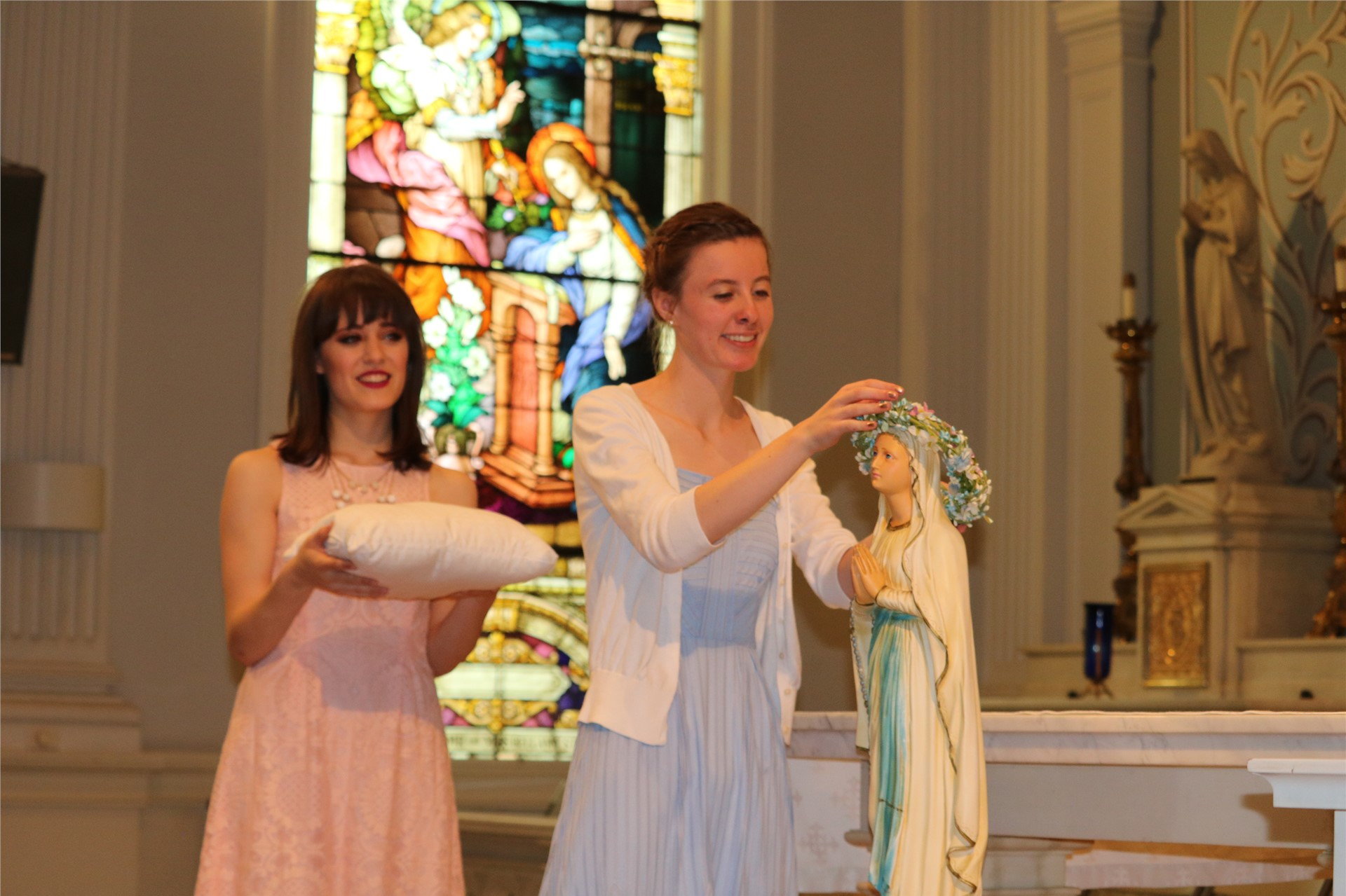 Sarah Tippenhauer and Gabby Silvestri crown Mary during the May Crowning ceremony